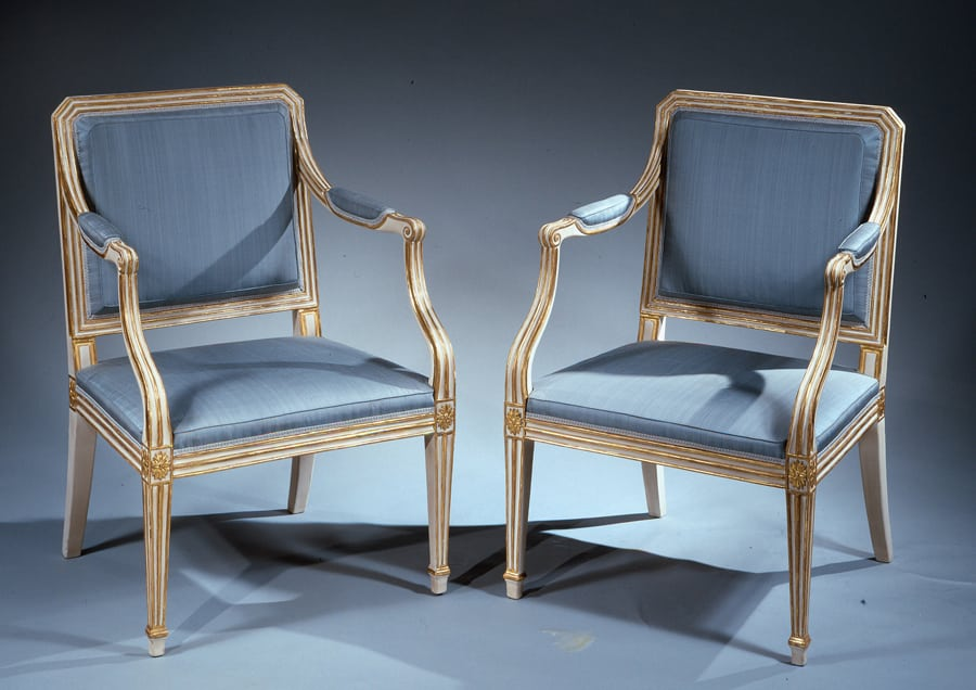 A pair of painted and gilt arm chairs.